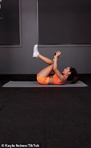 For added resistance, she held a dumbbell and brought her knees up to her chest to perform the ab crunch