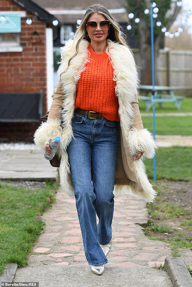 Funky: Chloe Sims opted to channel the 1970s with her fun and colourful look, teaming an orange chunky knit jumper with a cream suede coat with a fur trim
