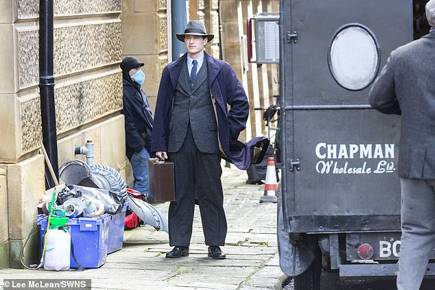 Pensive: The scenes saw Nicholas don a suit with a briefcase in hand as he strolled past vintage cars on the street