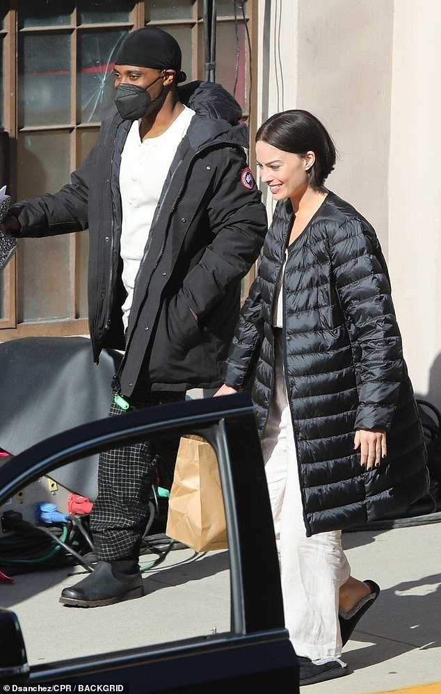 Happy: She appeared in very high spirits, while sharing a laugh with John David Washington between filming scenes in Pasadena, California