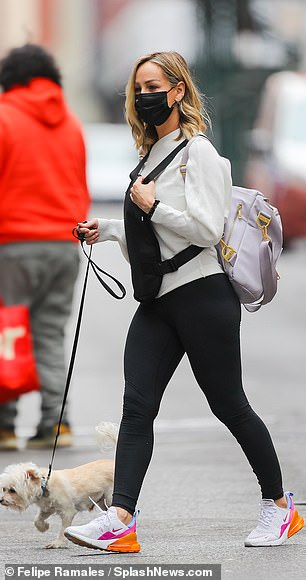 Athletic attire: Clare showed off her flair for athleisure in a unique cream colored sweatshirt paired with leggings as she pounded the pavement in sherbet-hued Nikes
