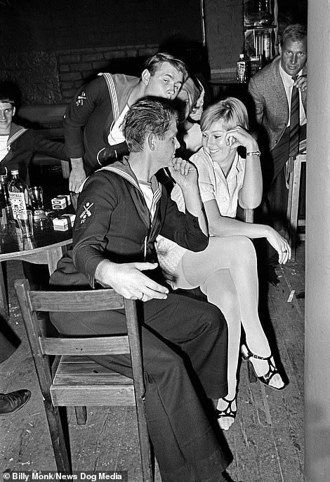 Two sailors are drawn to two blonde women inside The Catacombs bar, Cape Town, South Africa, Tuesday October 24, 1967