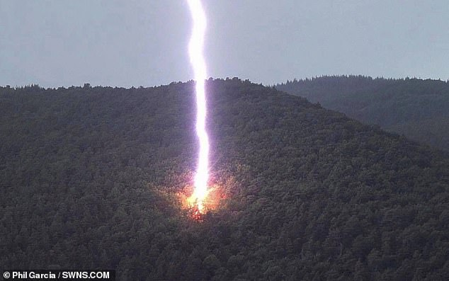 This incredible image captures a gigantic lightning bolt as it strikes the side of a mountain. The wild photo was taken last June by Phil Garcia, while out hiking with his friends in Pecos, New Mexico