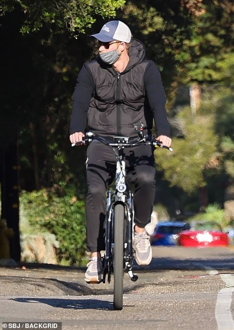 Harry, wearing a cap, sunglasses, mask and sportswear used the bike lane near the Sussexes u00A310million mansion