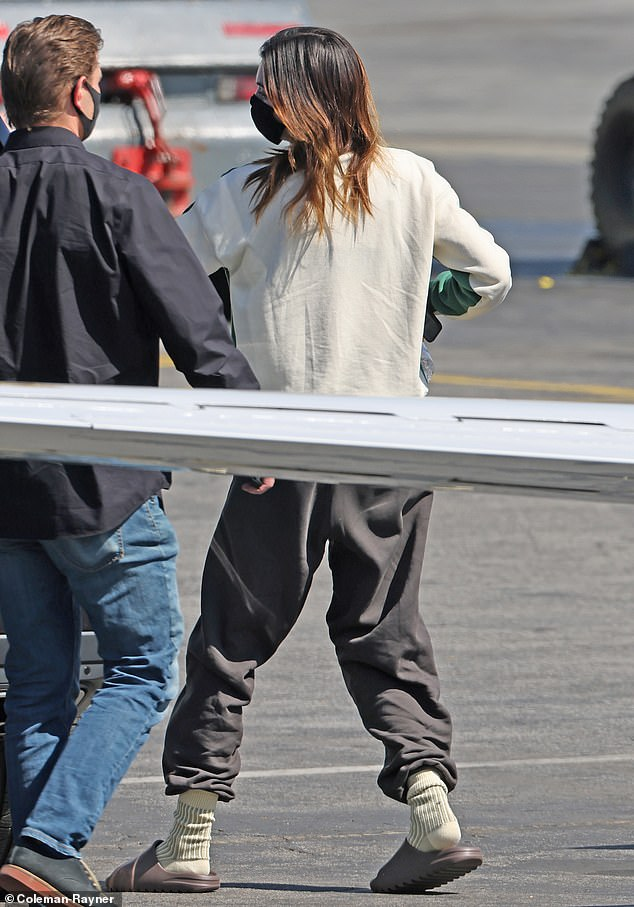 The love's still there: The reality television personality was seen wearing another pair of Yeezy slides as she walked across the tarmac