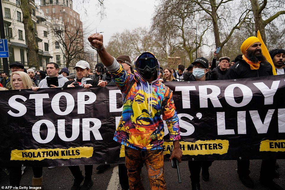 Protesters holding a banner saying 'stop destroying our kids' lives' and not wearing face masks march through the streets of London this afternoon