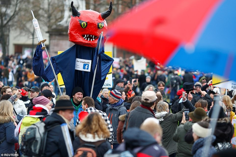 GERMANY: Protests against coronavirus restrictions also broke across Europe. In Kassel, a man holds a giant puppet depicting a devil with a vaccine