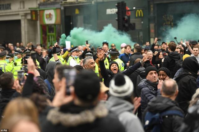 Demonstrators holding flares and filming with their phones surround police officers at the anti-coronavirus lockdown protest in London today