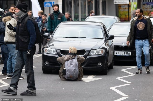 A protester sits in the middle of the road blocking traffic amid the demonstrations in London