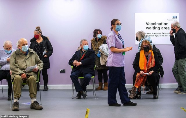 People wait to receive their injection of a Covid-19 vaccine at the mass vaccination hub at Robertson House in Stevenage, north of London, on January 11