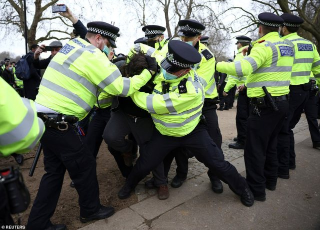 Police officers haul a demonstrator to the ground before cuffing him in Hyde Park during a protest against the coronavirus lockdown today