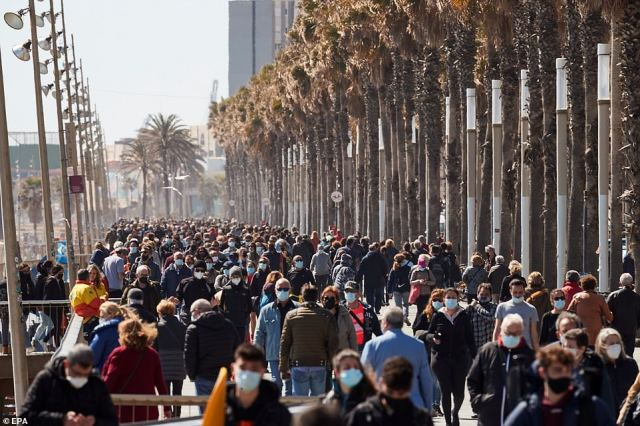 People walk along a sea promenade in Barcelona, Spain today.u00A0Madrid has seen a surge in tourism after city officials refused to follow the government's Covid curfew and let restaurants and bars stay open until 11pm