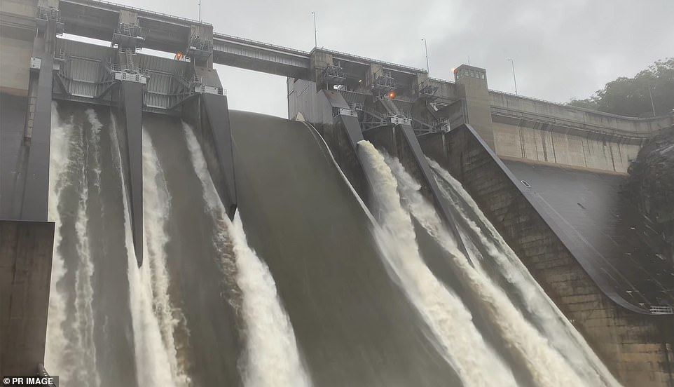 Warragamba Dam (pictured on Sunday) has began overflowing at the rate of 450 gigalitres a day, which would almost fill most of Sydney Harbour