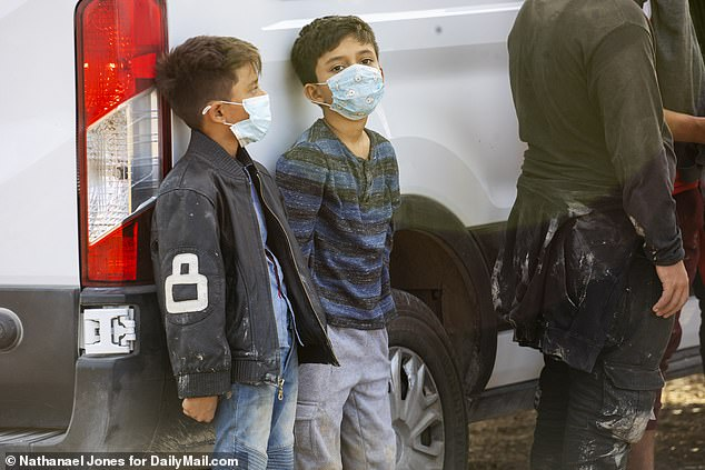 The number of migrant children in US custody has ballooned to nearly 15,500 as border officials struggle to find space to house them. Pictured: Two young boys who were separated from a large group of migrants wait to be taken to a special facility after illegally crossing into the US in Penitas, Texas, on March 12
