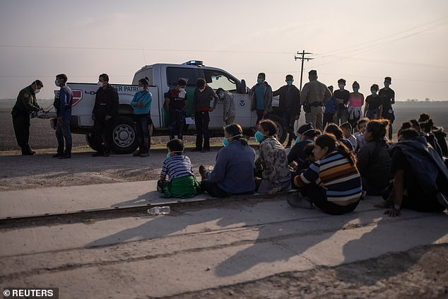 A US Border Patrol agent processes asylum-seeking unaccompanied minors as family units sit on the sideline after about 70 migrants crossed the Rio Grande river into US from Mexico on a raft in Penitas, Texas, on March 17