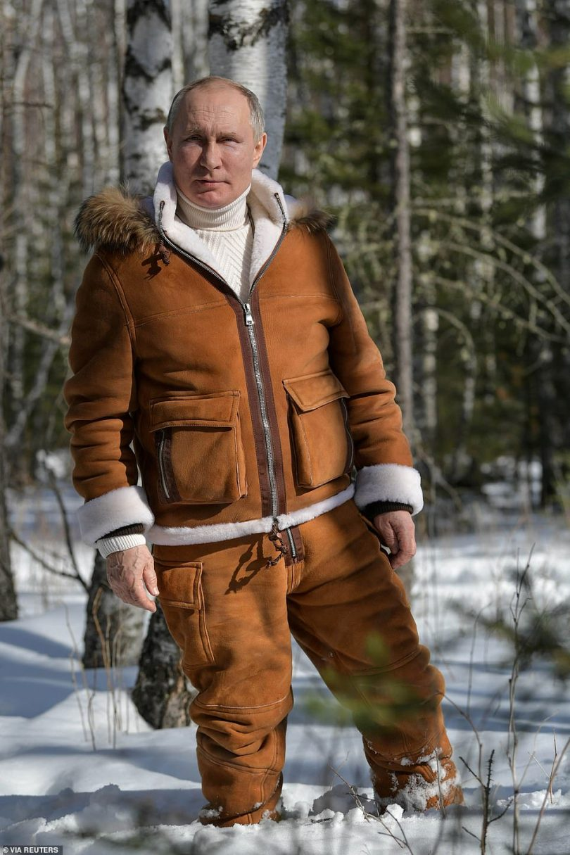 Russian President Vladimir Putin walks through snow during a holiday in the Siberian wilderness