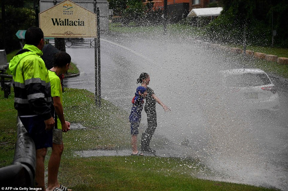 Children react as they are sprayed by floodwater from passing vehicles on a road near theu00A0Warragamba Dam