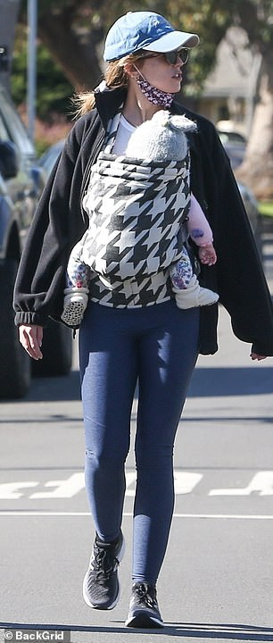 Baby's day out: She kept her daughter close for the outing as the baby kept warm in an adorable fuzzy grey beanie, pink top, floral printed legging and white booties