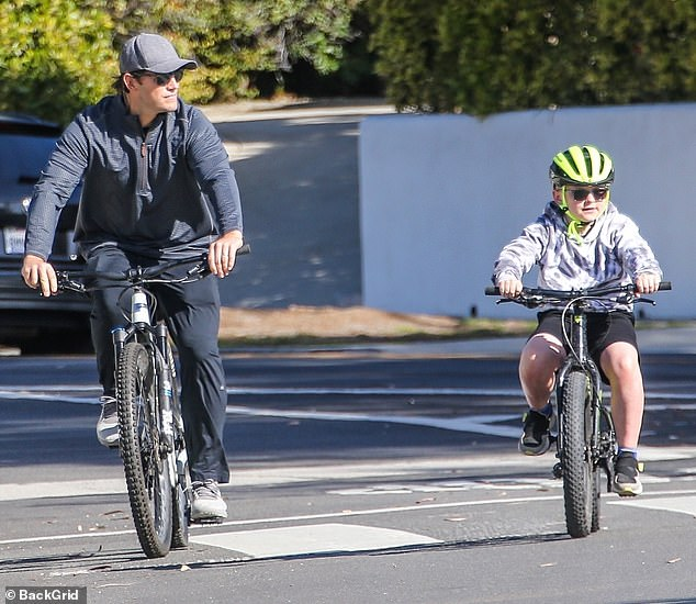 Dad duties: Chris wore a long-sleeve blue shirt and matching navy joggers, riding a bike alongside his son as they braved the busy LA streets. Jack stayed safe and stylish in his neon green helmet