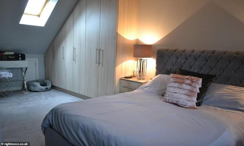 Relaxing: Katie and Carl's room that has an en suite shows a large double bed with grey carpet and made to measure wardrobes, providing the couple with the space they needed as they moved in together