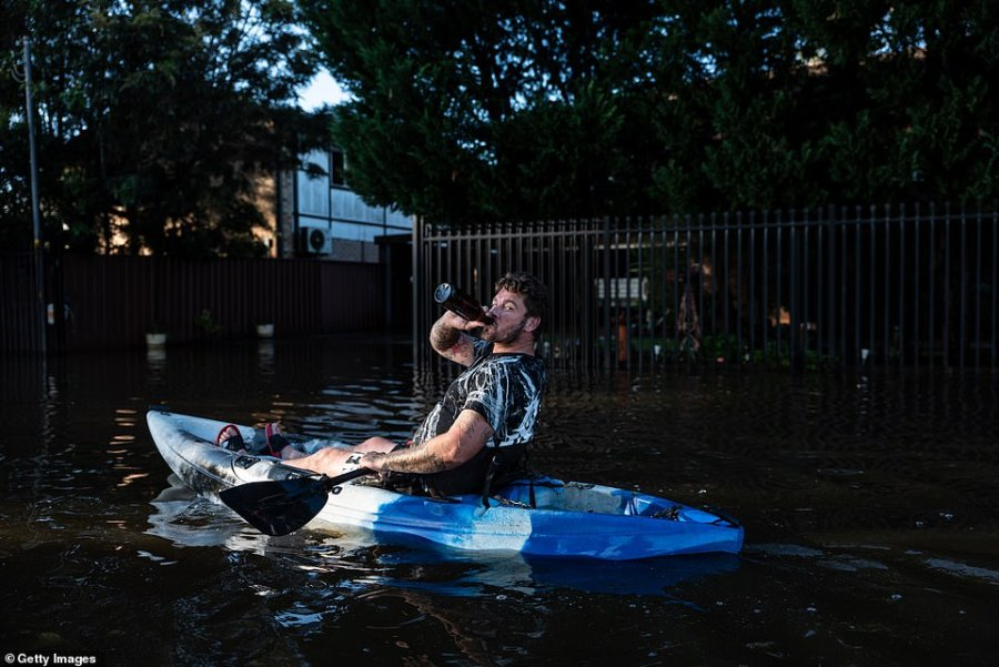 A man on a kayak makes the most of a bad situation by knocking back a beer as he paddles through floodwaters in Windsor