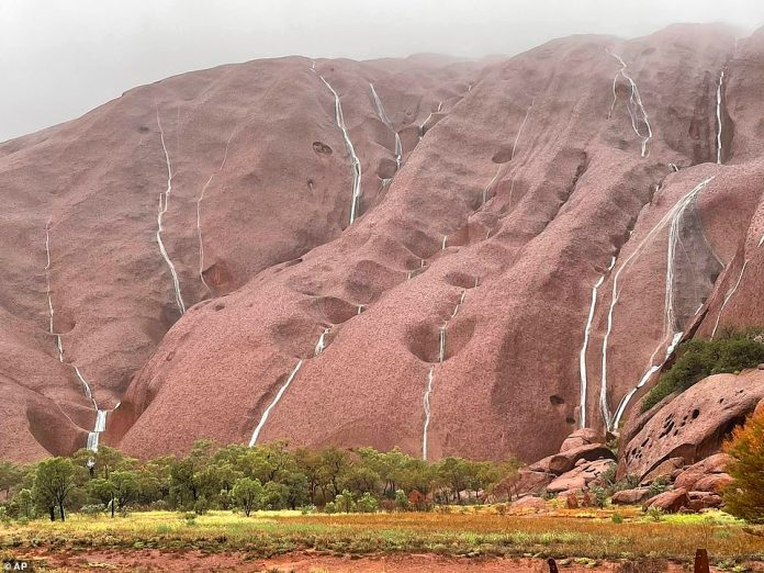 Once covered with tourists climbing up the rock, Uluru has turned into cascading waterfalls after nearly 50mm of rain over the weekend.