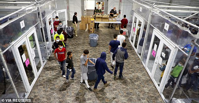 Migrant children stand in line inside a temporary processing facility in Donna, Texas, to get access to essentials while other children held in cage-like tents look on and wait their turn