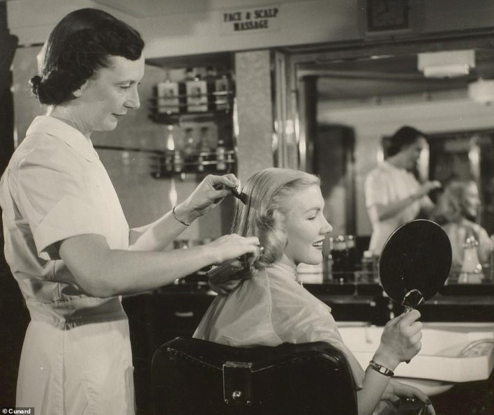 A passenger assesses her haircut in the Queen Mary beauty parlour. The image dates to the 1960s