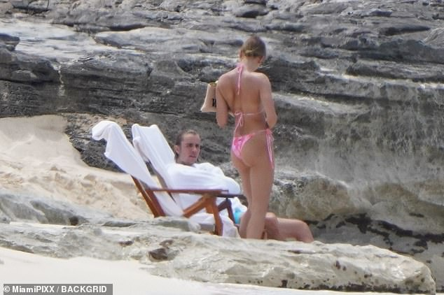 Beach babes: Hailey showed off her supermodel frame and golden tan in a fluorescent pink string bikini with a matching floral print