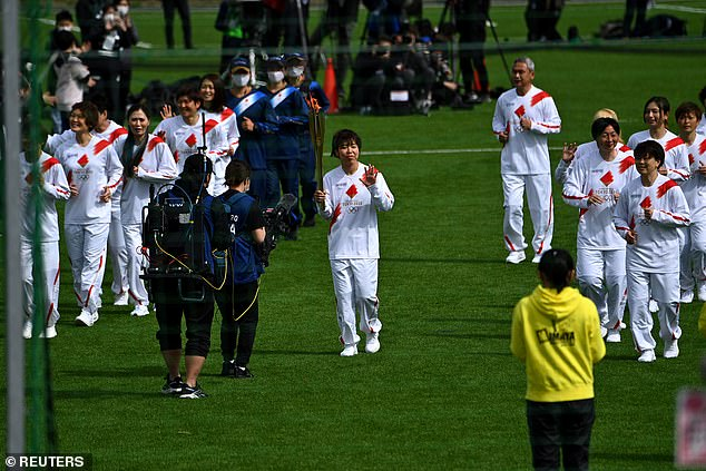 Japanese torchbearer Azusa Iwashimizu, a member of the Japan women's national football team, carries a torch during the Tokyo 2020 Olympic Torch Relay