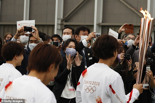 Supporters are seen wearing masks as they try to get a glimpse of the members of Nadeshiko Japan