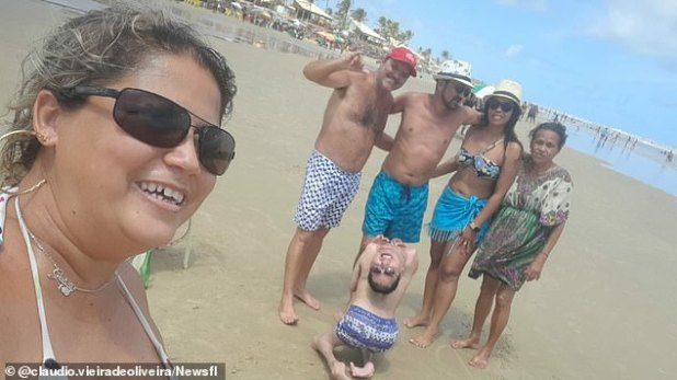 'Claudinho' has not let his disability prevent him from leading a busy and happy life.  In the photo above, 'Claudinho' and his friends enjoy a day at the beach