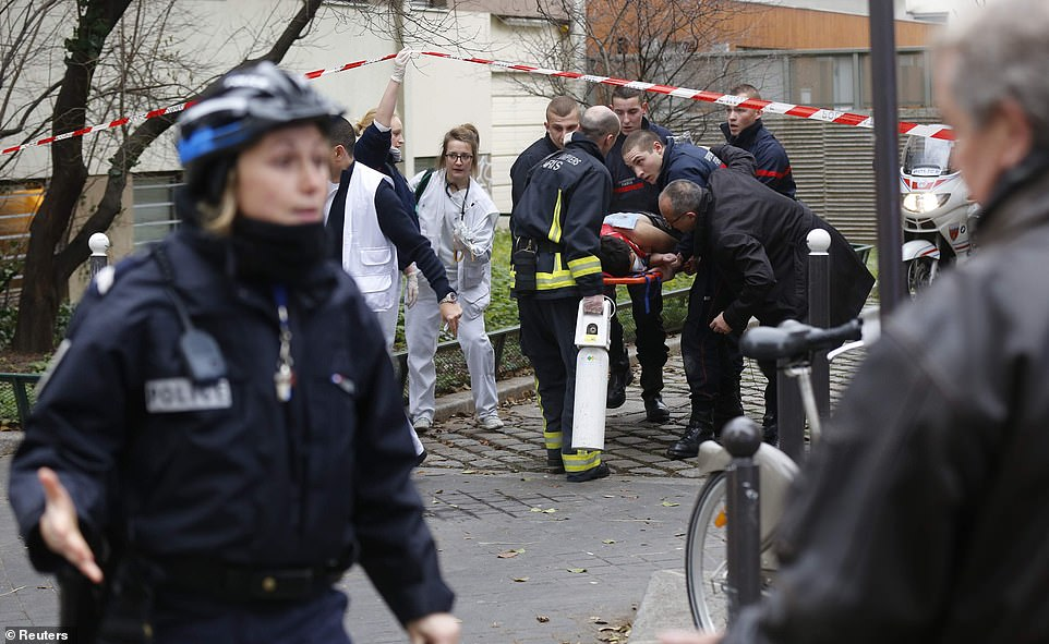 Firefighters carry a victim on a stretcher at the scene after the shooting at the Paris offices of Charlie Hebdo in January 2015