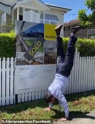 Akermanis performs a handstand outside a home he recently sold