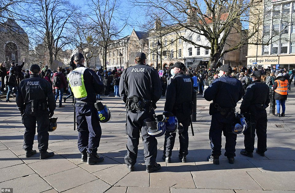 Police officers with helmets and batons ready stand watch on College Green this afternoon