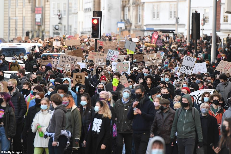Hundreds of demonstrators are seen pouring through the streets of Bristol this afternoon, the third such demonstration in the city centre since Sunday