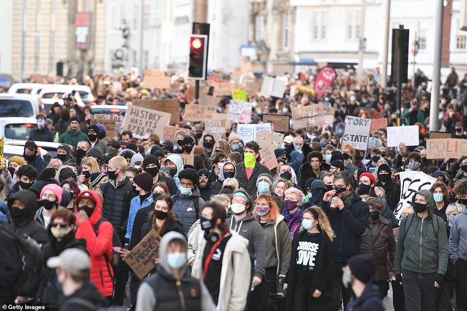 Demonstrators holding protesters denouncing the legislation and referring to a 'Tory police state' are held up by activists in Bristol this evening