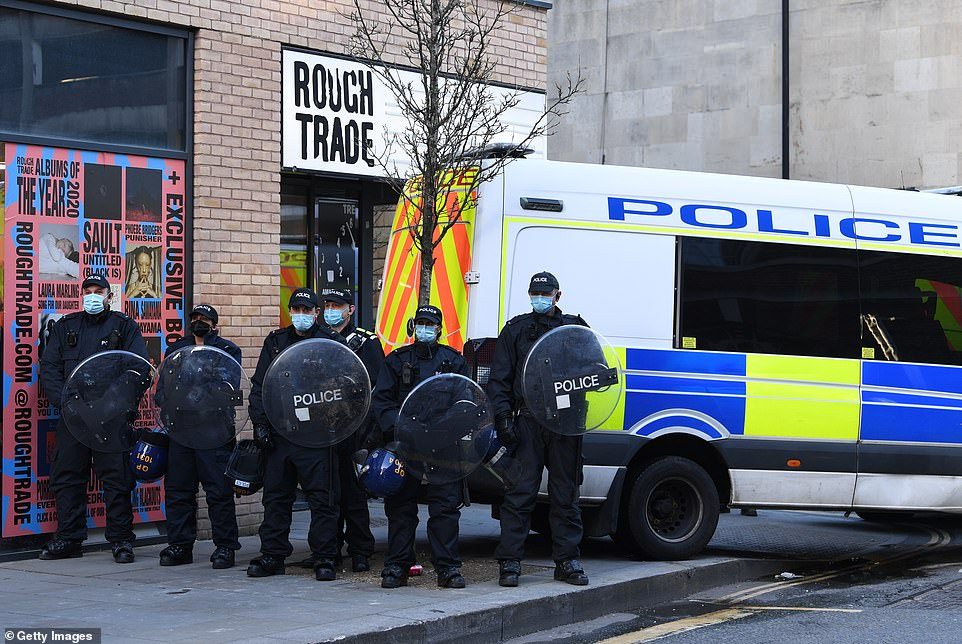 Riot police hold up shields beside a van parked across the road as they face-off with demonstrators for a third time in a week