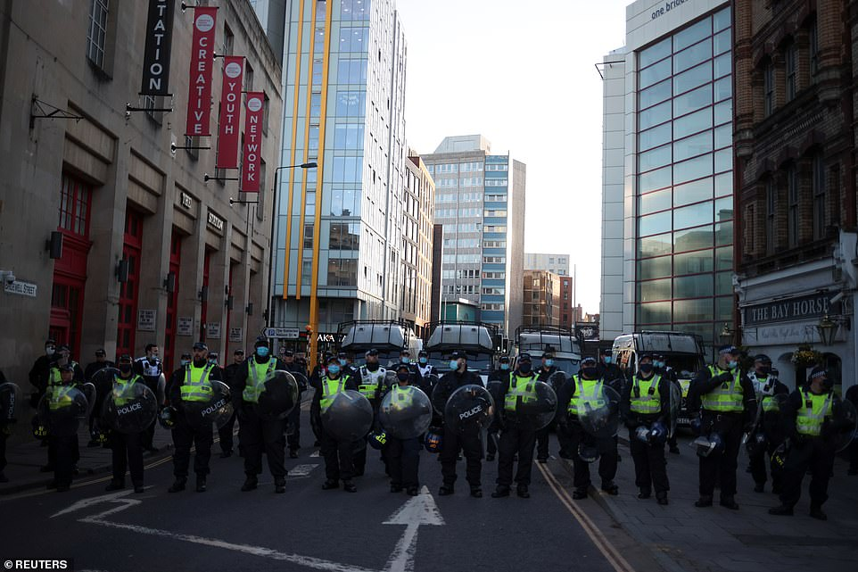 Pffocers stand guard to prevent demonstrators from making their way to Bridewell police station, the scene of the weekend's riot