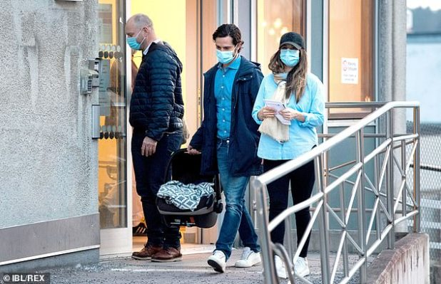 Princess Sofia could be seen clutching a notepad as her husband carried their third child as they left the hospital today (pictured)