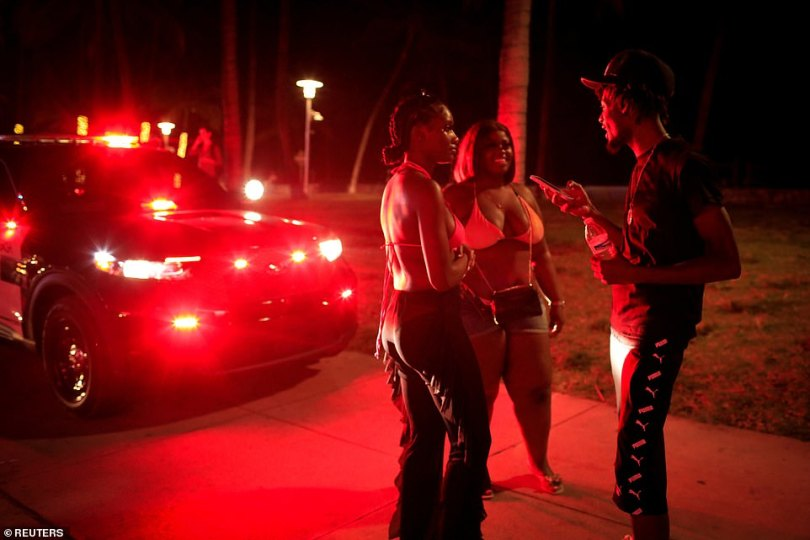 A group of partygoers convene in front of a squad car as police tell people to leave the area
