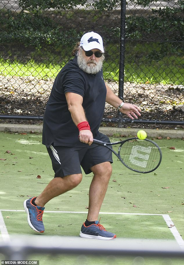 Casual: The 56-year-old Hollywood star dressed for the match in an all-black ensemble of a baggy T-shirt and shorts