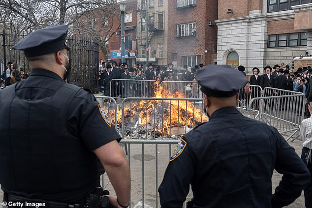 NYPD officers stand guard while Orthodox Jews participate in the 'biur chametz,' a burning leavened food ritual, before the week-long Passover holiday amid the coronavirus pandemic