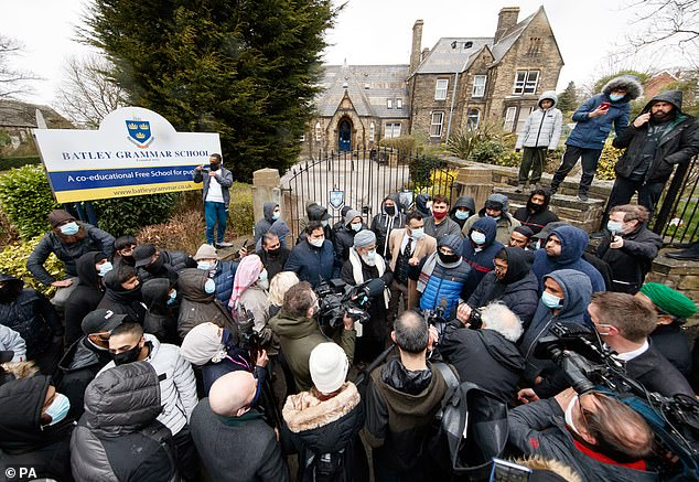 Protestors are pictured giving a statement to members of the media on Friday outside Batley Grammar School near Bradford, West Yorkshire, where a teacher has been suspended for reportedly showing a caricature of the Prophet Muhammad during a religious studies lesson