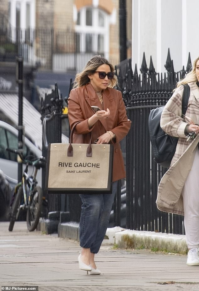 Back on dry land! The former S Club 7 star, 42, donned an over-sized leather blazer in a tan hue while she clutched a stunning Saint Laurent bag and high heels