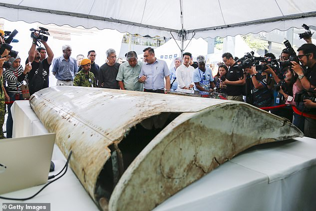 Malaysian Minister of Transport Anthony Loke (centre) looks at the wing flap found on Pemba Island, Tanzania, in 2019 which has been identified a missing part of Malaysia Airlines Flight MH370