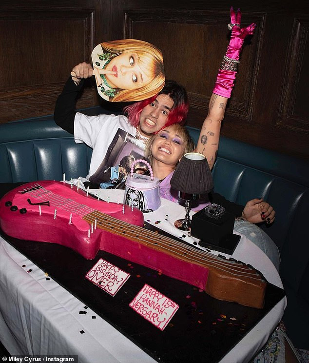 Special occasion: Cyrus was seen posing behind a guitar-shaped cake with her pal Omer Fedi; the event was also meant as a birthday celebration for the musician