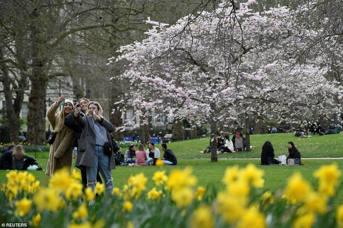 People relax in St. James's Park on Saturday ahead of lockdown restrictions being eased on Monday, March 29