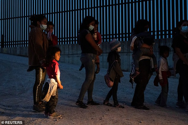Asylum-seeking migrants' families make a line to board a bus as they wait to be transported by the U.S. Border Patrols after crossing the Rio Grande river into the United States from Mexico in Penitas, Texas, on Friday