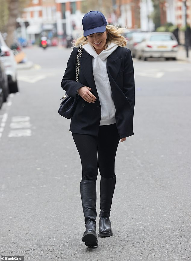 Stylish: Mollie cracked a smile as she crossed the road on her way into the London-based studio and kept the look edgy with some chunky black high-knee boots from Russell & Bromley